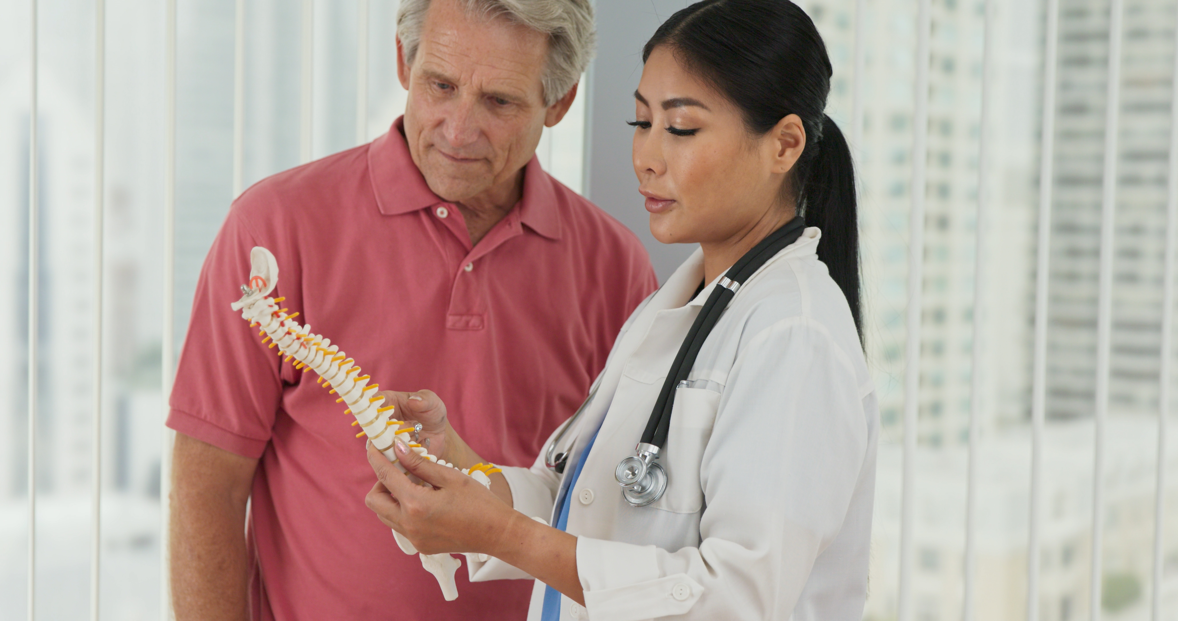 Physical therapist or chiropractor talking to aging man about treatment
